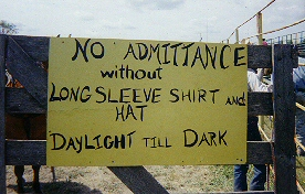 Sign on rodeo gate requiring long sleeve shirts