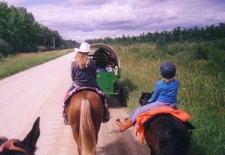 Two young riders, one with a cowboy hat and one with a helmet