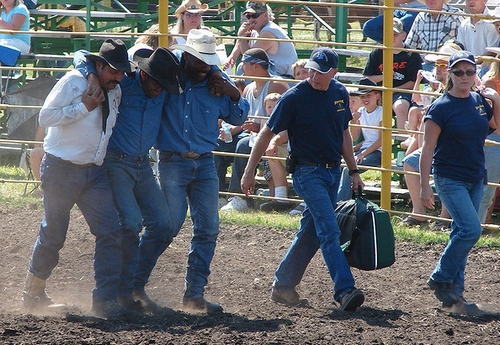 Rodeo contestant being helped away from a good ride
