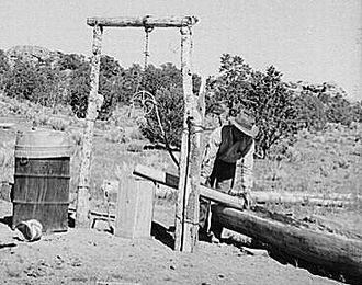 Faro Caudill pouring water from his well into watering trough made of hollowed-out log. Pie Town, New Mexico